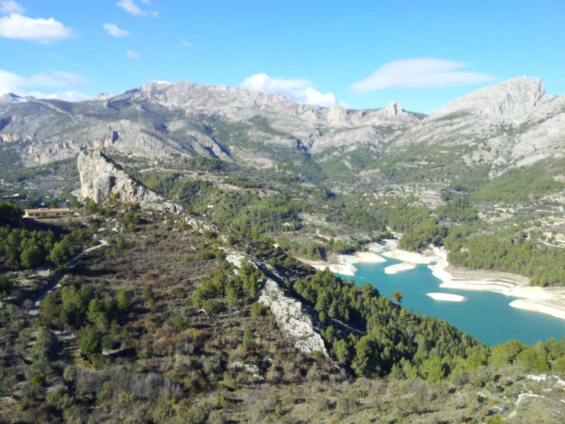 Blue lake, mountains surrounding, rocks and pine trees.