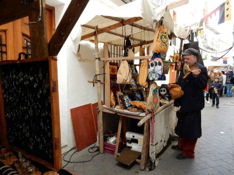 Street market, wooden stalls, leather goods, sewing machine.