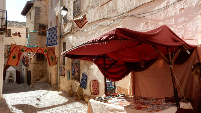 White walls, market stall, flags and tapestry.