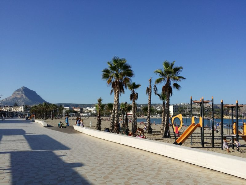 Tiled promenade by beach, palm trees, play equipment.