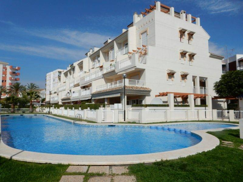 Las Dunas apartments white building swimming pool