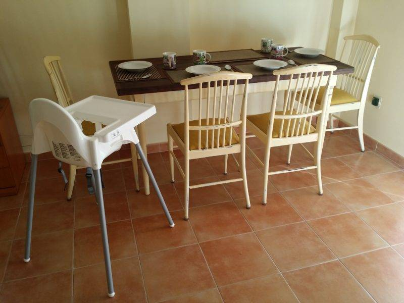 Wooden topped table, yellow chairs, highchair, tiled floor.