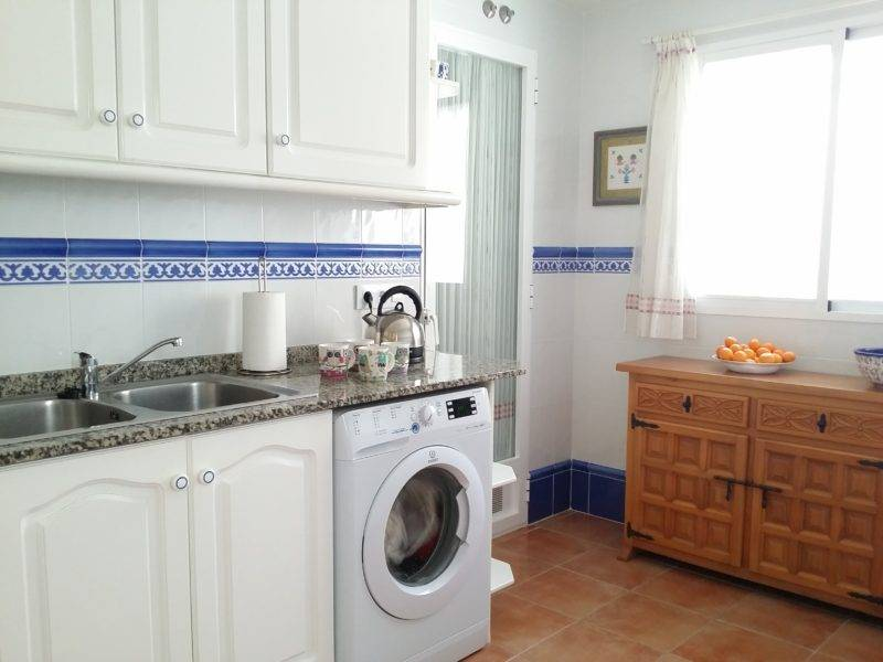 Kitchen, washing machine, sink, wooden sideboard, kettle, cups.